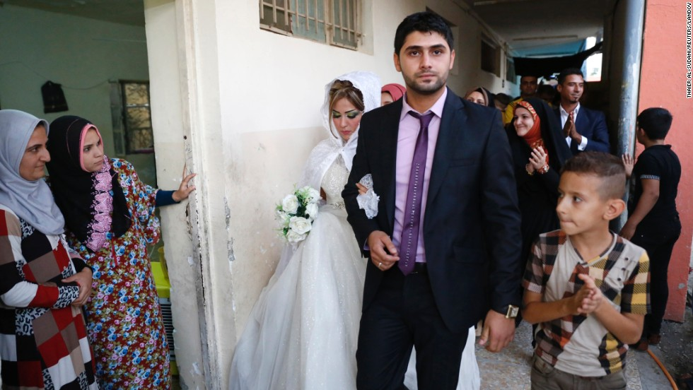 Mohammed Harith Youssif, a displaced Iraqi Shiite, walks with his Sunni bride, Reem Ahmed, during their wedding Monday, September 1, at a school in Baghdad. The couple fled to Baghdad after the militant group ISIS advanced into their hometown of Mosul, Iraq.