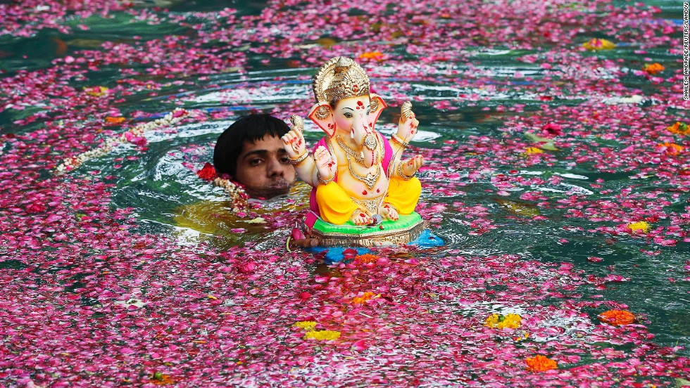 A man immerses an idol of the Hindu elephant god Ganesh in an artificial pond Saturday, August 30, during the 10-day Ganesh Chathurthi festival in Mumbai, India.