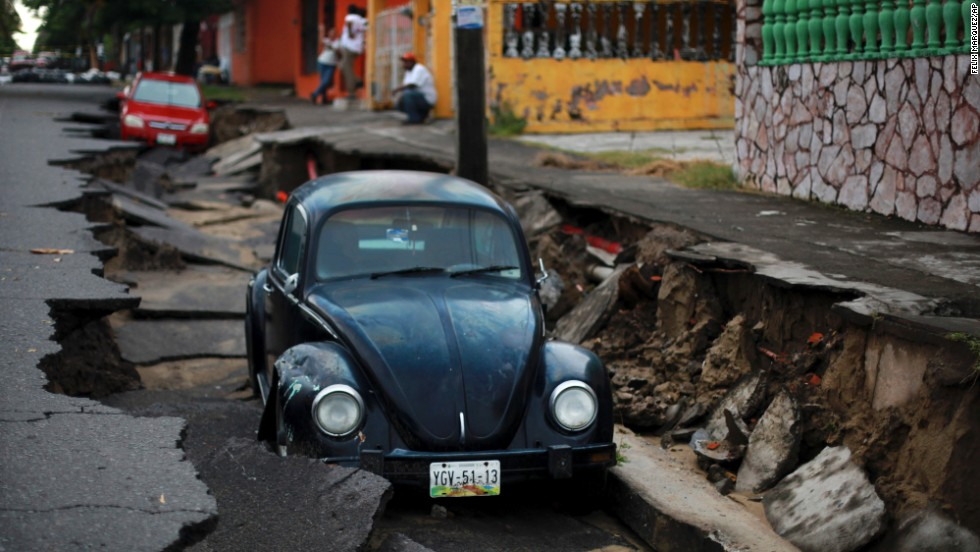 Cars sit on a street that collapsed after heavy rain in Veracruz, Mexico, on Tuesday, September 2.