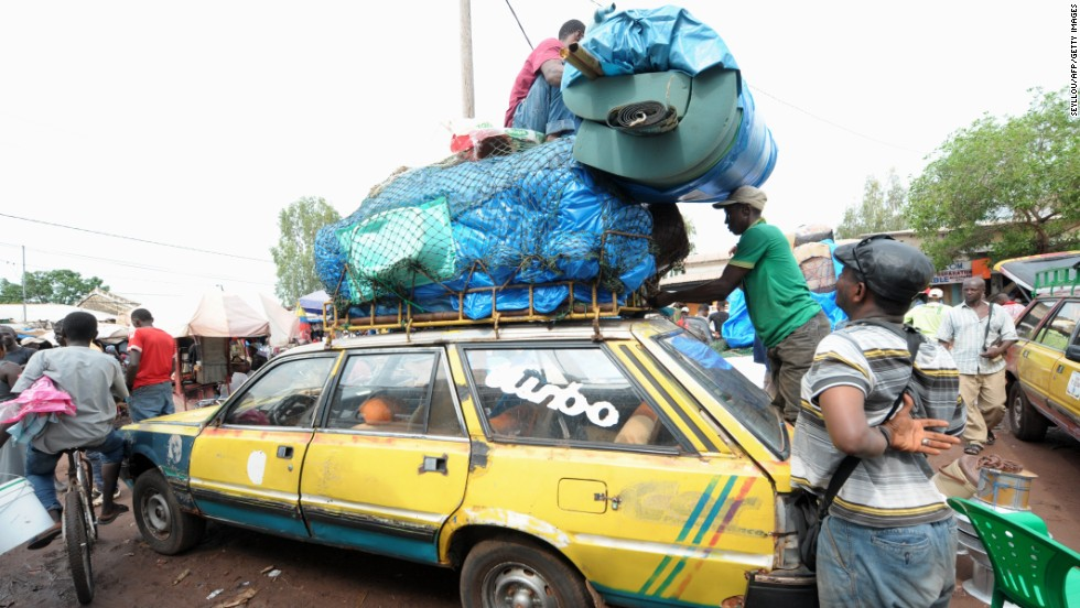 After an Ebola case was confirmed in Senegal, people load cars with household items as they prepare to cross into Guinea from the border town of Diaobe, Senegal, on September 3, 2014.
