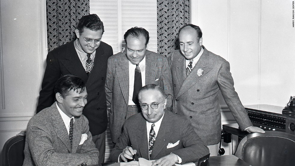 For publicity purposes, Clark Gable, the overwhelming popular choice to play Rhett Butler, pretends to sign a contract for the film under the watchful eye of producer Selznick, standing, far left, and MGM studio chief Louis B. Mayer, seated right. The star had been reluctant to tackle the role, fearing he wouldn't be able to live up to the public's expectations. With Gable now available, Selznick had to move quickly to start filming.