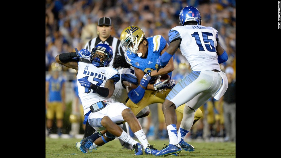 UCLA wide receiver Eldridge Massington loses his helmet after a hit from Memphis' Chris Morley, left, during a football game between the two schools Saturday, September 6, in Pasadena, California. UCLA won 42-35 to improve to 2-0 on the season.