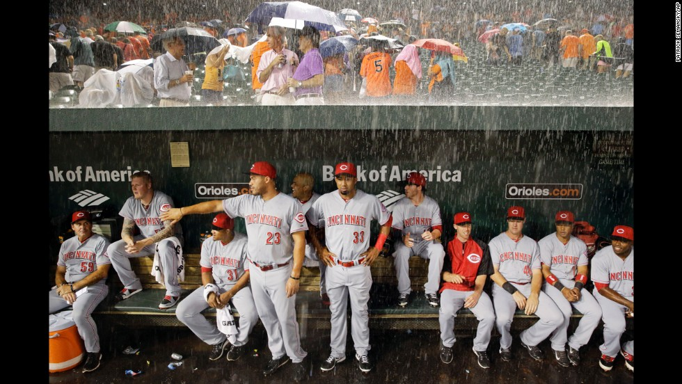 The Cincinnati Reds wait in the dugout as heavy rain falls during a delayed game in Baltimore on Tuesday, September 2.