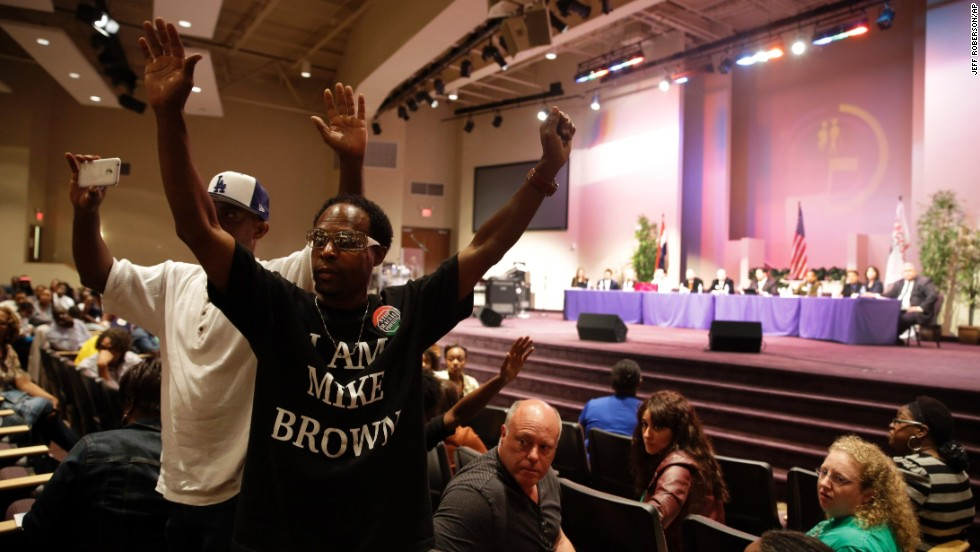Marurice Brown raises his arms during the public comments portion of the meeting.