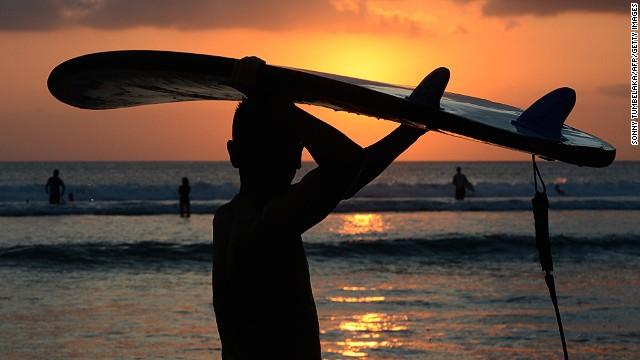 A Balinese surfer carries a surfboard at sunset along Kuta beach.
