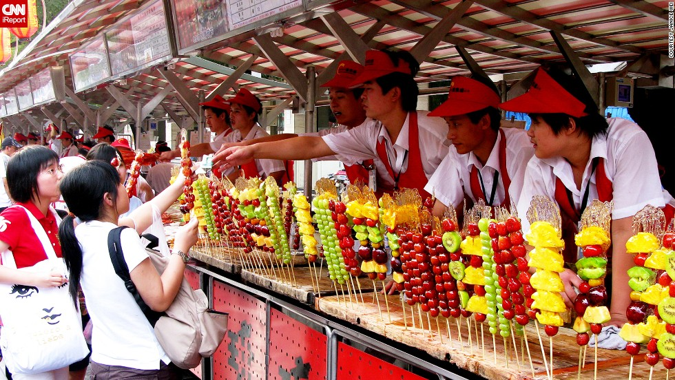 "Skewers of sweet pineapple, tart green grapes, and other colorful arrangements of fruit line a concession stand in<a href=""http://ireport.cnn.com/docs/DOC-1156894""> Beijing, China</a>."