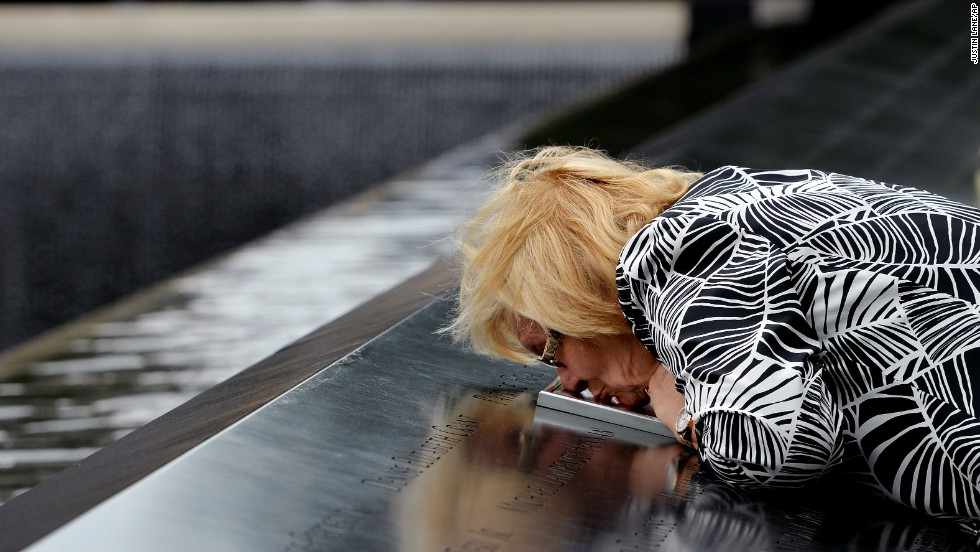 Paola Braut, of Belgium, kisses a photograph of her son Patrice along the edge of the North Pool of the World Trade Center site.