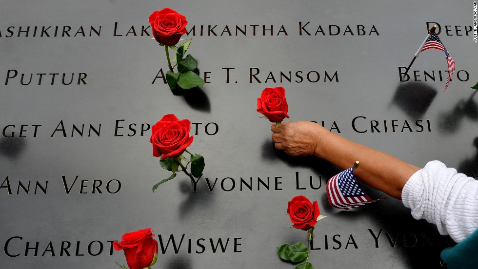 "A woman places flowers along the edge of the North Pool at the World Trade Center site in New York on Thursday, September 11. This year marks the <a href=""http://www.cnn.com/2014/09/11/us/gallery/9-11-memorial-2014/index.html"">13th anniversary</a> of the September 11 terrorist attacks that killed nearly 3,000 people in New York, Washington and western Pennsylvania."