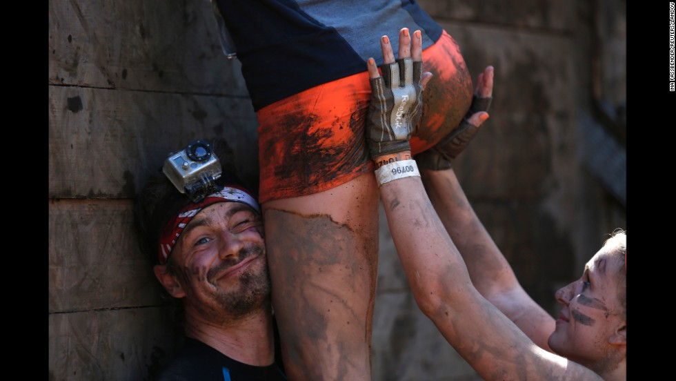 "People work together to climb over a wall during a ""Tough Mudder"" obstacle race Saturday, September 6, in Arnsberg, Germany."