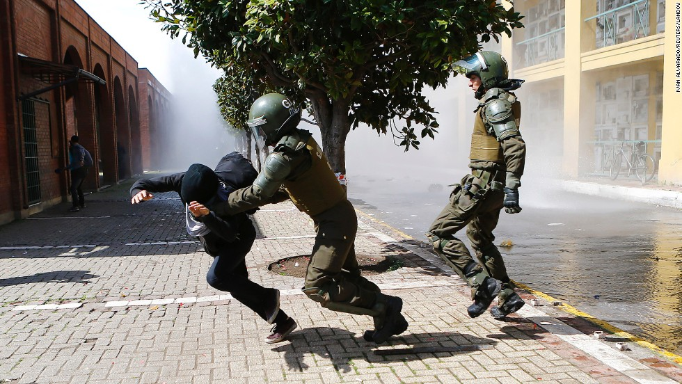A demonstrator is detained by riot policemen Sunday, September 7, during a protest marking the 1973 military coup in Santiago, Chile.