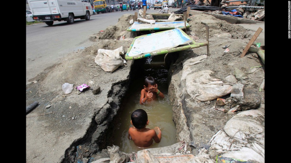 Children play in the murky waters of an open drainage being repaired by workers in Manila, Philippines, on Monday, September 8.