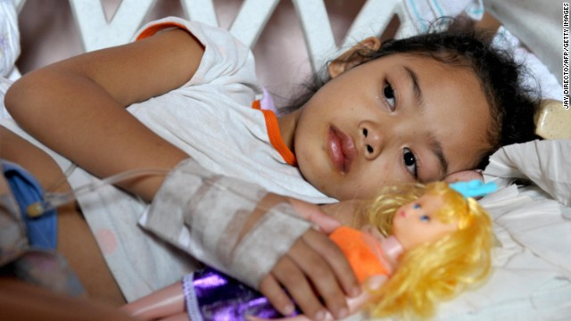 Lika Rose Caticon, 7, who is suffering from Typhoid fever, holds a doll as she lies in a makeshift cot at the overcrowded JP Rizal Memorial District Hospital in Calamba City south of the Philippine capital Manila on March 5, 2008.