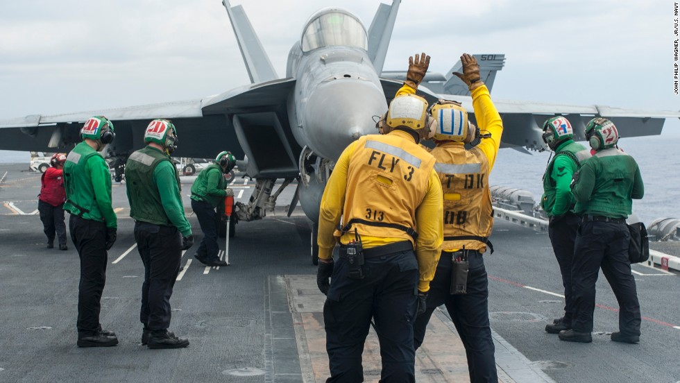 An F/A-18E Super Hornet from the Sunliners of Strike Fighter Squadron 81 taxis onto a catapult before launching from the flight deck of the aircraft carrier USS Carl Vinson.