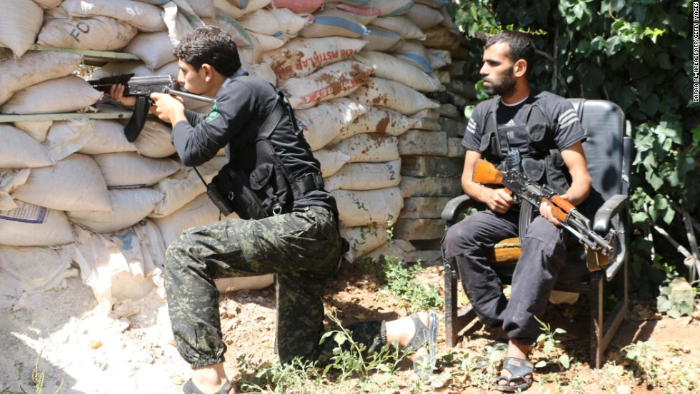 Syrian opposition fighters take position behind sandbags in Aleppo on Thursday, September 11.