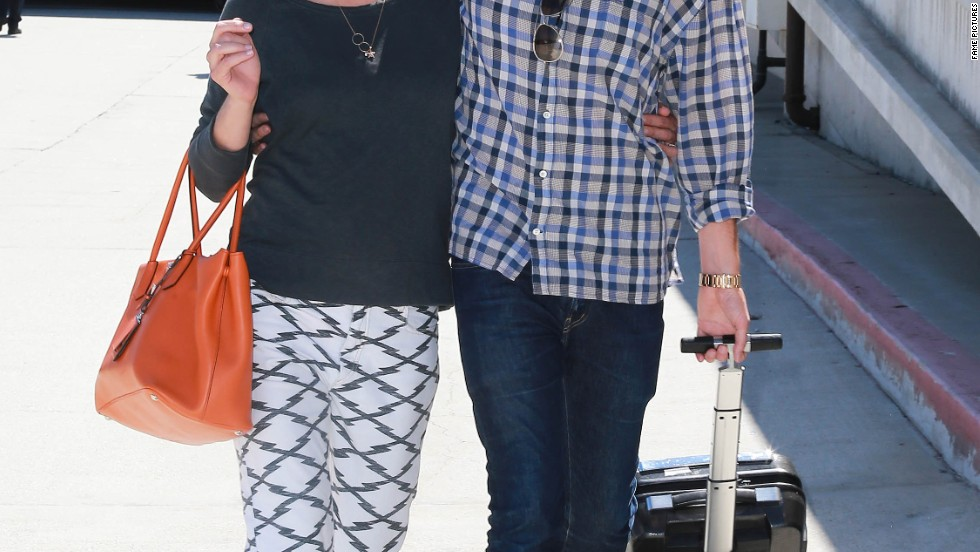 Expectant parents Milla Jovovich and Paul Anderson make their arrival at LAX on September 11.
