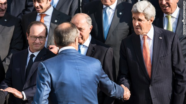French President Francois Hollande, left,  watches U.S Secretary of State John Kerry, right, shaking hands with Russian Foreign Minister  Sergey Lavrov, back to the camera, before a family photo at the international conference intended to come up with an international strategy against  Islamic State extremists, in Paris, Monday, Sept. 15, 2014. As diplomats from around the world sought a global strategy to fight Islamic State extremists, Iran ruled out working with any international coalition, saying it had rejected American requests for cooperation against the militants. Partially hidden at center is French Foreign Minister Laurent Fabius. (AP Photo/Brendan Smialowski; Pool)