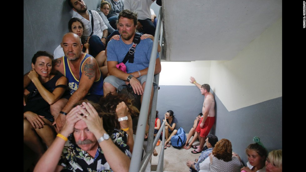 Tourists sit in a stairwell after a resort's shelter was damaged September 15 in Los Cabos.