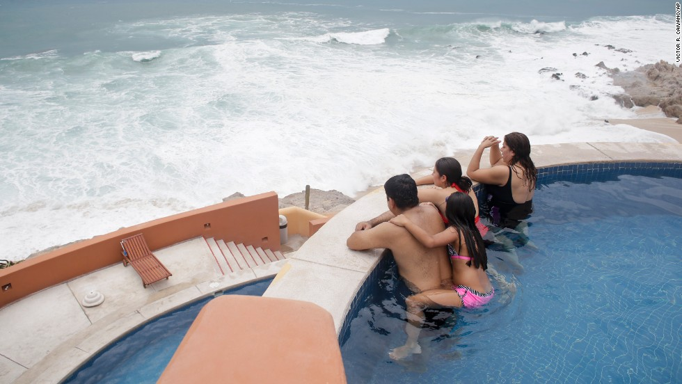Tourists watch the ocean from inside a swimming pool at a resort in Los Cabos on September 14.
