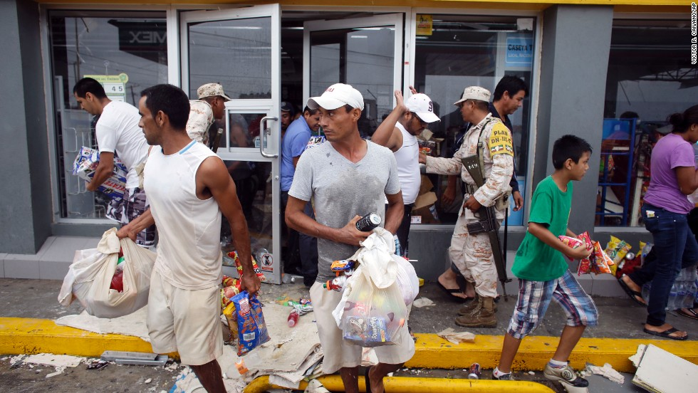 People take items from a Los Cabos convenience store that was destroyed by Hurricane Odile on September 15.