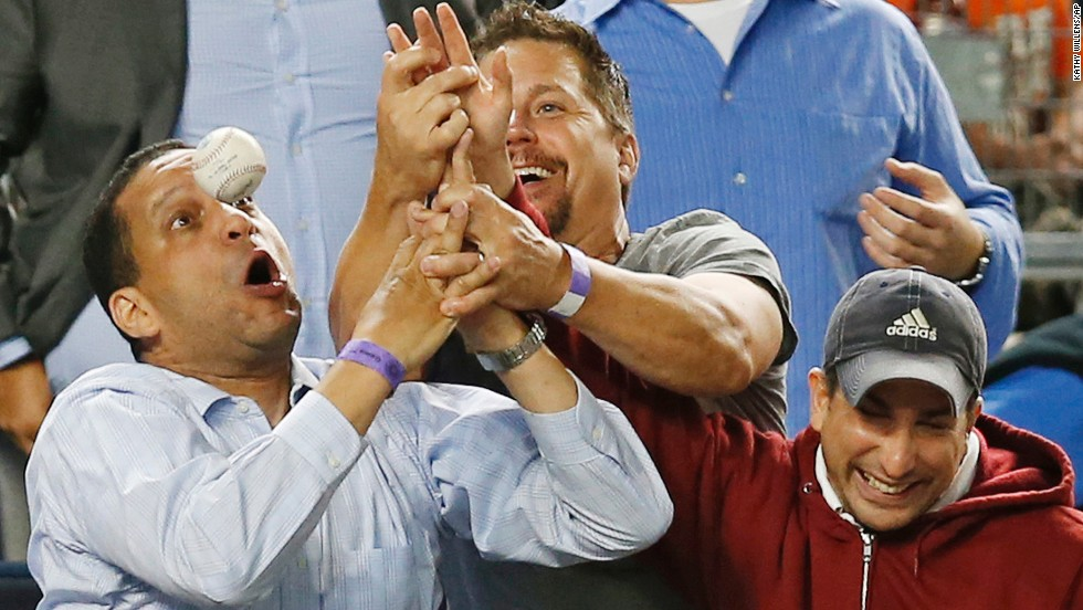 Three baseball fans in New York try to catch a foul ball during the Major League Baseball game between the New York Yankees and the Tampa Bay Rays on Tuesday, September 9.
