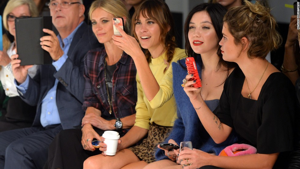 Celebrities including Alexa Chung and Pixie Geldof whip out their smartphones on the front row at London Fashion Week