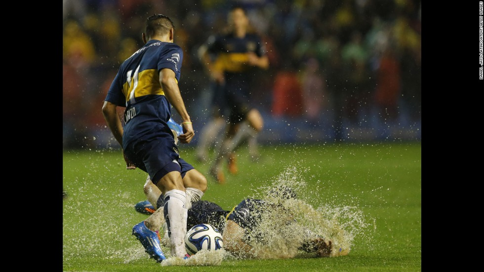 Jonathan Calleri of Argentine soccer club Boca Juniors falls down next to teammate Federico Carrizo during a match against Racing Club on Sunday, September 14. The match in Buenos Aires was postponed shortly after halftime because the field was too soaked by rain.