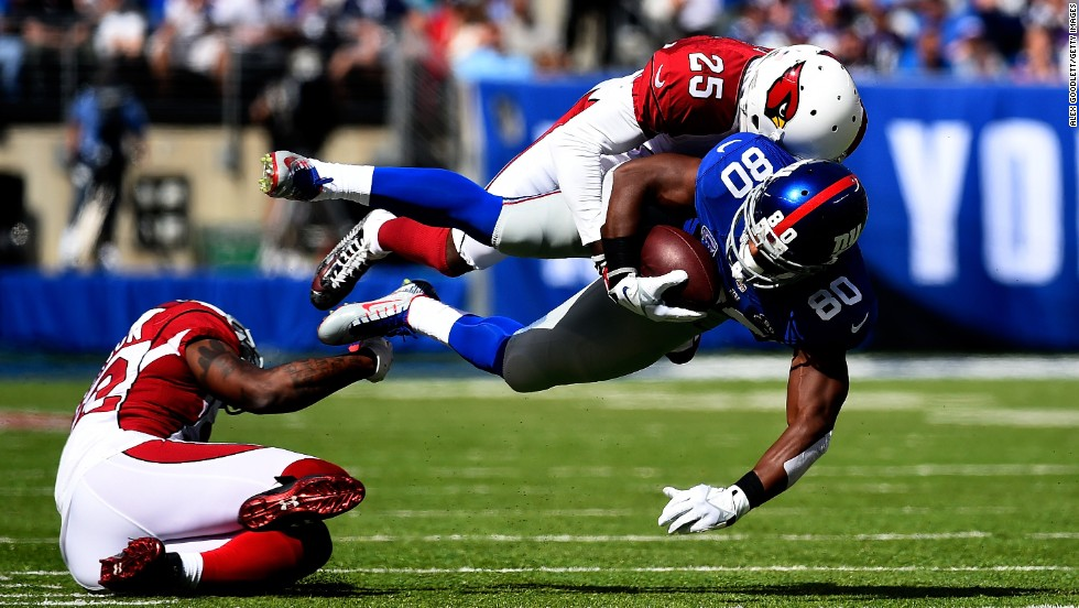 New York Giants wide receiver Victor Cruz is tackled by Arizona Cardinals cornerback Jerraud Powers during an NFL game Sunday, September 14, in East Rutherford, New Jersey. The Cardinals defeated the Giants 25-14 to stay undefeated through two games.