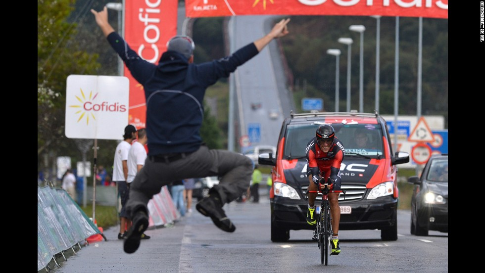A cycling fan leaps in front of Philippe Gilbert during the final stage of the Tour of Spain on Sunday, September 14. Alberto Contador won the overall race.