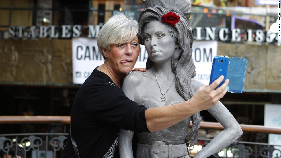 A woman takes a selfie with a new statue of the late singer Amy Winehouse on Monday, September 15, in London. Winehouse would have been 31 on September 14.