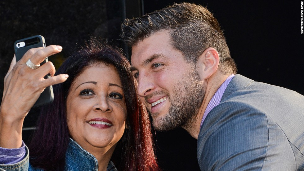 "Tim Tebow, the former football player who is now a television personality, smiles for a fan's photo as he leaves a ""Good Morning America"" taping Monday, September 15, in New York."