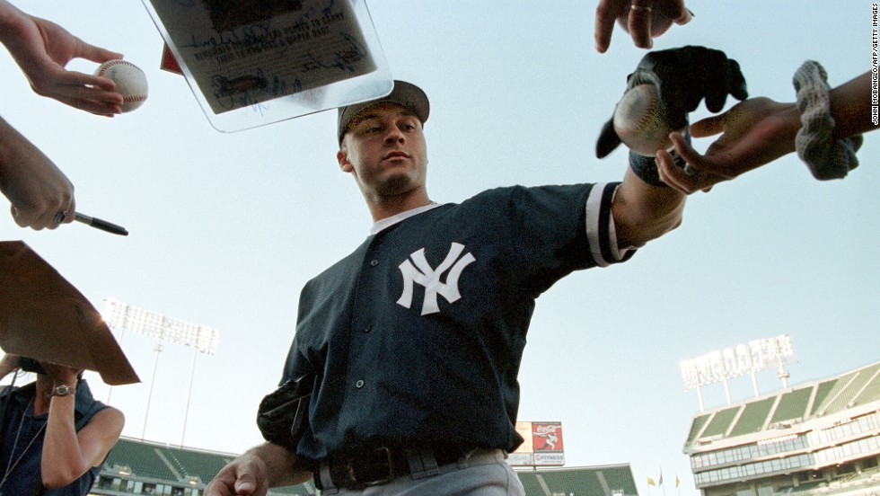 Jeter signs autographs before a game in Oakland in August 1998.
