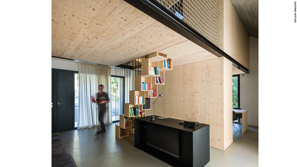 Made of stone and wood, Solid House in Slovenia features a bookshelf that doubles as stairs to its upper level. Slovenia will host Open House events October 3-5.