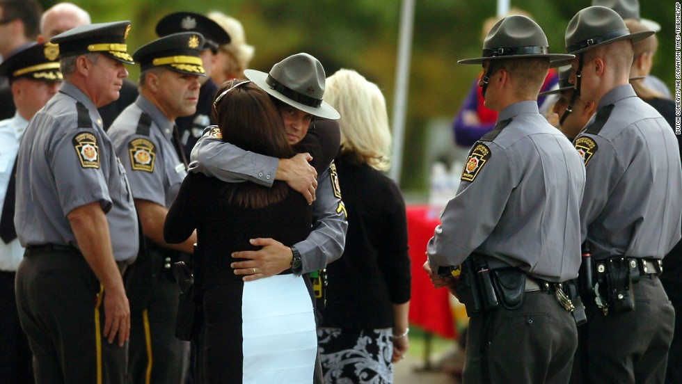 A woman embraces a Pennsylvania state trooper during the viewing of Dickson's body Wednesday, September 17, in Scranton.