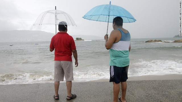 Caption:Two men observe the step of the Tropical Storm Polo in Acapulco, Guerrero State, Mexico on September 17, 2014. The storm swirled off the southwestern coast and was expected to become a hurricane late Wednesday or early Thursday, the US forecasters said. AFP PHOTO/Pedro Pardo (Photo credit should read Pedro PARDO/AFP/Getty Images)
