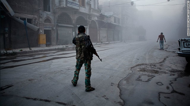 A rebel fighter stands on a street covered with dust following a reported air strike by Syrian government forces in the old city of Aleppo on July 21, 2014.