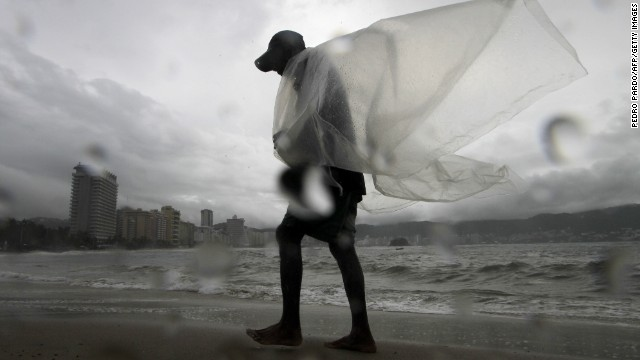 A man walks by a beach during the passage of the Tropical Storm Polo in Acapulco, Guerrero State, Mexico on September 17, 2014. The storm swirled off the southwestern coast and was expected to become a hurricane late Wednesday or early Thursday, the US forecasters said. AFP PHOTO/Pedro Pardo (Photo credit should read Pedro PARDO/AFP/Getty Images)