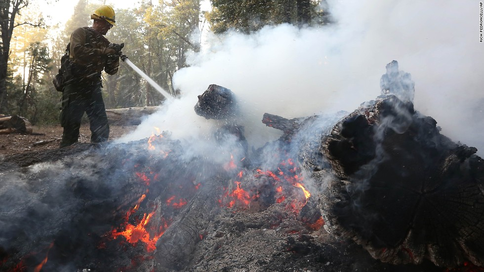 A U.S. Forest Service firefighter pours water on burning embers while clearing hot spots of the King Fire near Georgetown, California, on Thursday, September 18.