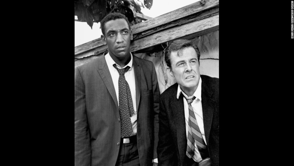 "Cosby won three Emmys for his portrayal of Alexander Scott, an Oxford-educated spy who travels undercover with his tennis-playing partner, Kelly Robinson (Robert Culp) in ""I Spy,"" which aired on NBC from 1965 to 1968. Cosby was the first African-American to star in an American dramatic series."
