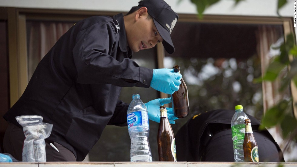 A forensic investigator examines a bottle at a hotel room close to where the couple was found.