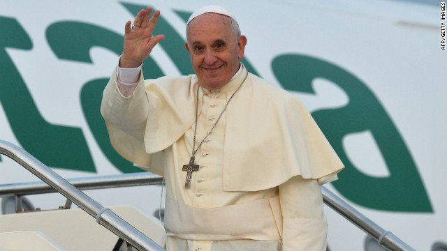 Pope Francis waves from the top of the stairs leading to the plane that will carry him to Tirana, on September 21, 2014 at Rome's Fiumicino international airport