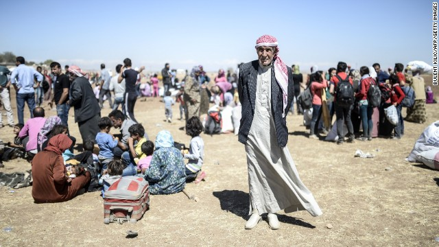 Caption:Syrian Kurds rest after crossing the border between Syria and Turkey near the southeastern town of Suruc in Sanliurfa province, on September 20, 2014. A man carries an elderly Syrian Kurd after they crossed the border between Syria and Turkey near the southeastern town of Suruc in Sanliurfa province, on September 20, 2014. Several thousand Syrian Kurds began crossing into Turkey on September 19 fleeing Islamic State fighters who advanced into their villages, prompting warnings of massacres from Kurdish leaders. Turkey on September 19 reopened its border with Syria to Kurds fleeing Islamic State (IS) militants, saying a 'worst-case scenario' could drive as many as 100,000 more refugees into the country. AFP PHOTO/BULENT KILIC (Photo credit should read BULENT KILIC/AFP/Getty Images)