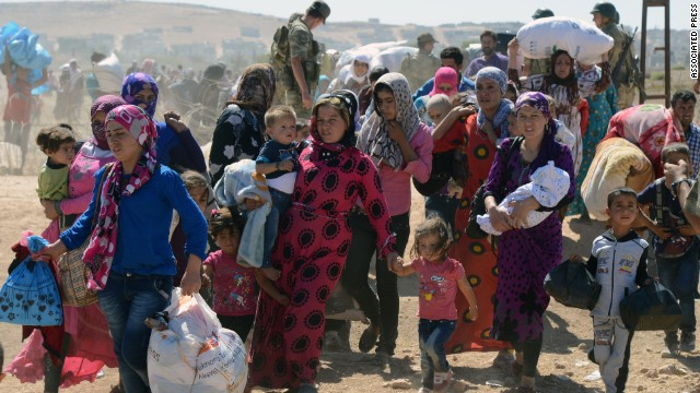 Syrian refugee women and children gather at the border in Suruc, Turkey, Saturday, Sept. 20, 2014. TSeveral thousand Syrians, most of them Kurds, crossed into Turkey on Friday to find refuge from Islamic State militants who have barreled through dozens of Kurdish villages in northern Syria in the past 48 hours. (AP Photo)