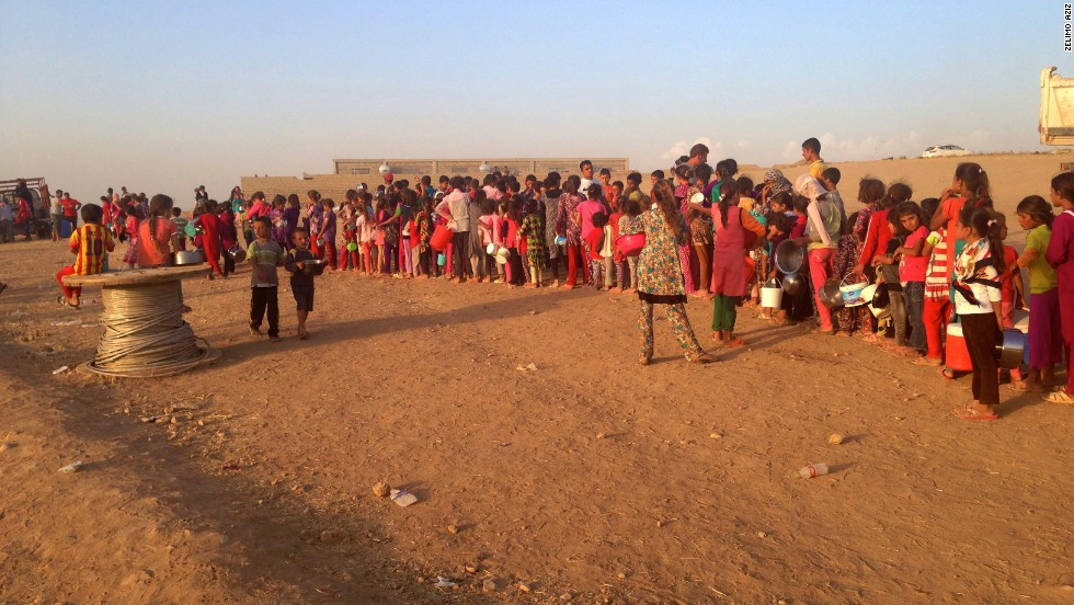 The refugees of the Khanke refugee camp wait in a line with buckets for water.