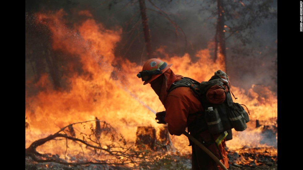A firefighter hoses down hot spots during a controlled burn to fight the King Fire near Placerville, California, on Monday, September 22. The King Fire is one of 10 wildfires raging across California.