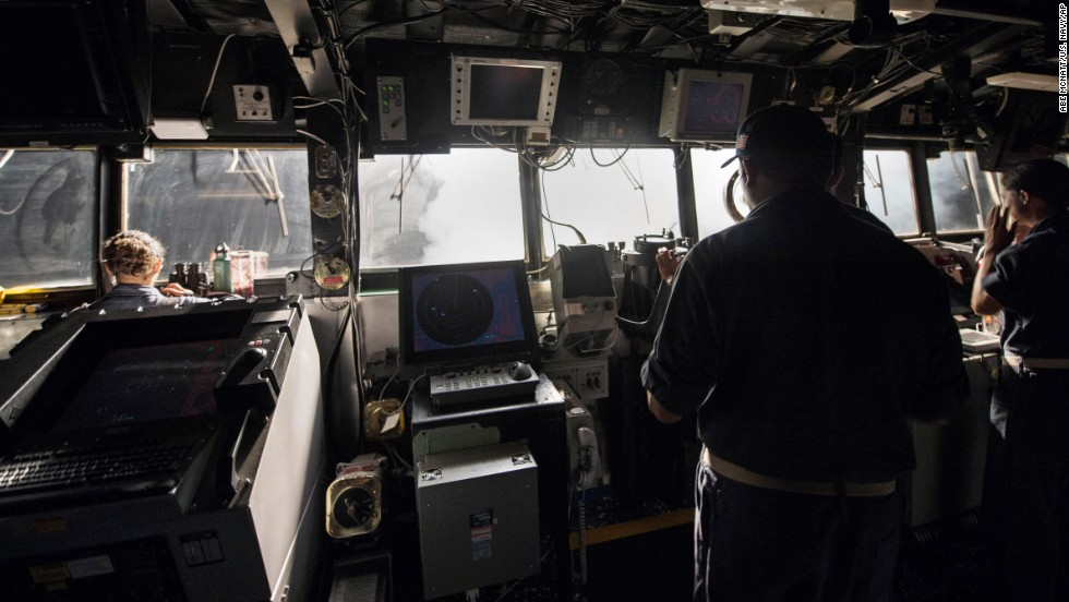 U.S. sailors stand on the bridge of the USS Philippine Sea while Tomahawk cruise missiles are launched toward targets in Syria on September 23.