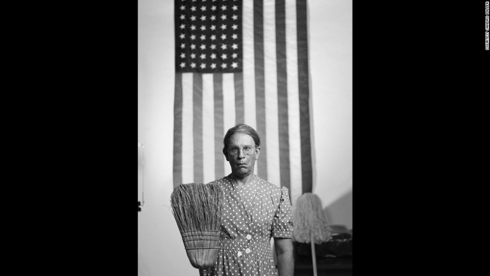 "Malkovich mimics the ""American Gothic, Washington D.C.""  photo that was taken by Gordon Parks in 1942."