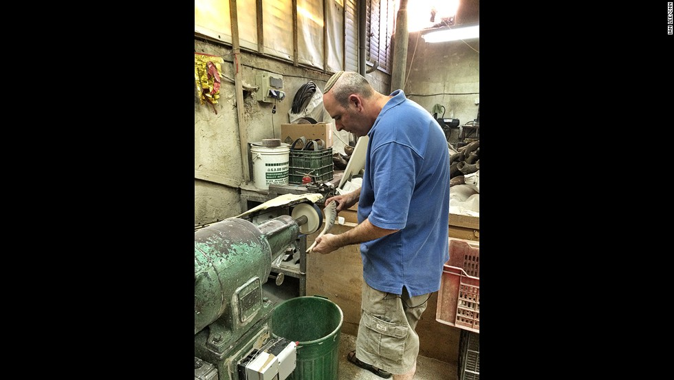 Eli Ribak starts grinding a raw ram's horn in the first stage of turning it into a shofar.
