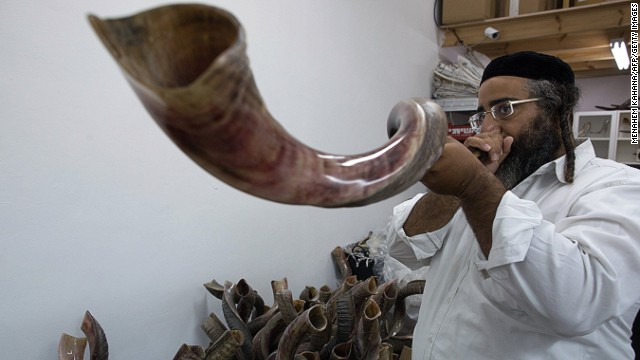 An Ultra-Orthodox Jewish man tests a Shofar (a religious musical instrument made from a ram's horn) before buying it at a factory in Tel Aviv on September 22, 2014 ahead of the Jewish New Year.