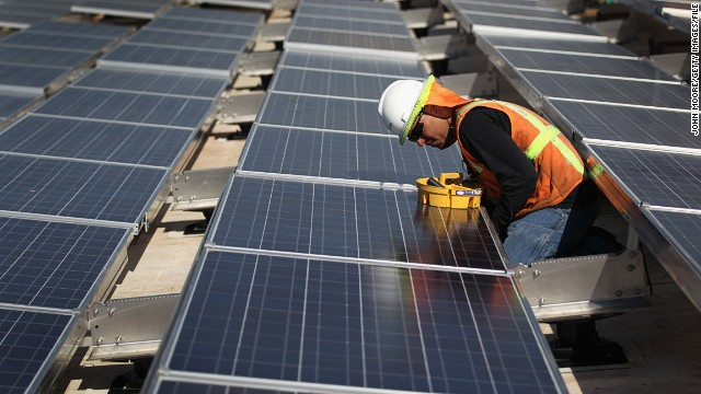 A worker finishes installing solar panels on October 1, 2010.