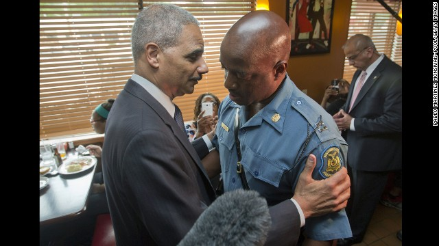 U.S. Attorney General Eric Holder talks with Capt. Ron Johnson, right, of the Missouri State Highway Patrol on August 20, 2014 in Ferguson, Missouri.